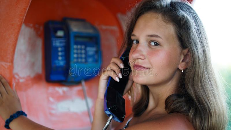 Portrait of happy and smiling girl talking in the phone booth on the city street stock photography