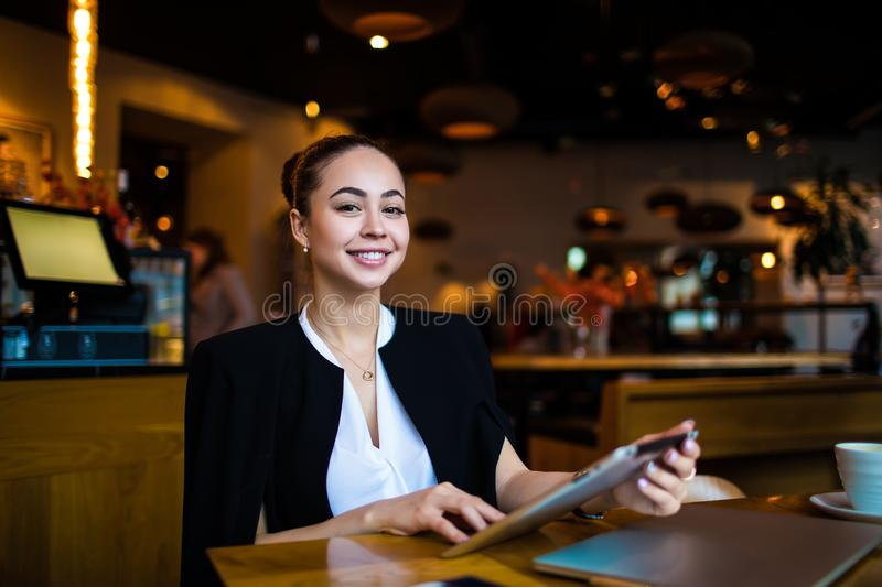 Portrait of a happy smiling gorgeous woman owner successful restaurant holding touch pad royalty free stock photo