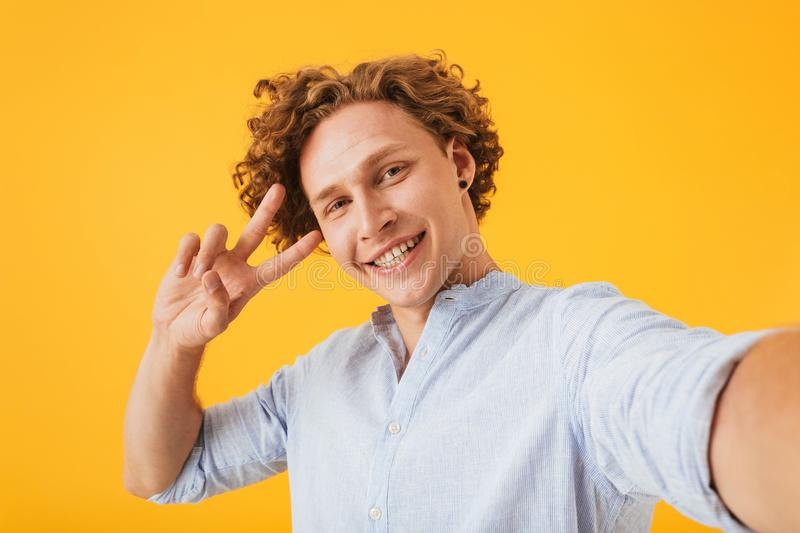Portrait of happy smiling guy 20s taking selfie photo and showing peace sign, isolated over yellow background royalty free stock image