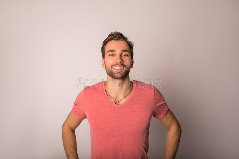Portrait of a happy smiling handsome male dressed in fashionable t-shirt with copy space stock image