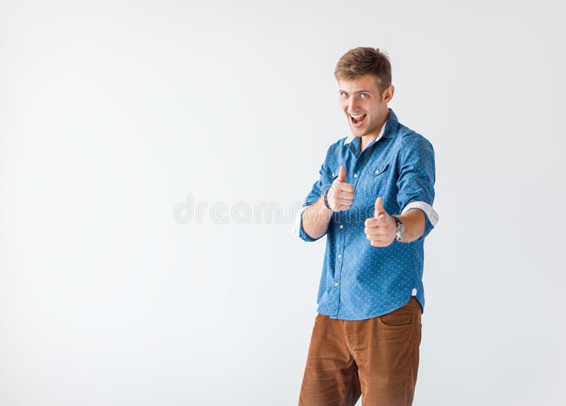 Portrait of happy smiling handsome man giving thumbs up sign stock photo