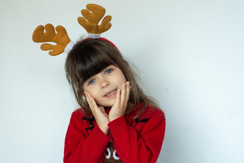 Portrait of happy smiling kid in a red knitted pullover with a Santa hat on head isolated on white background. Merry xmas. Moose horn. Carnival costume stock photos