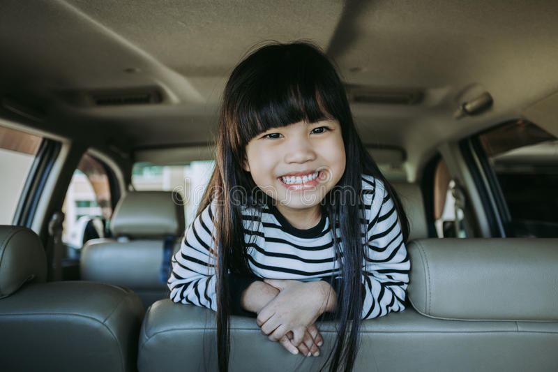 Portrait happy, smiling kid sitting in the car looking out windows, ready for vacation trip.  royalty free stock image