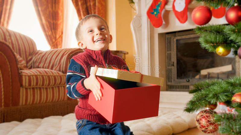 Portrait of happy smiling little boy holding and opening big box with gifts on Christmas or New Year royalty free stock image