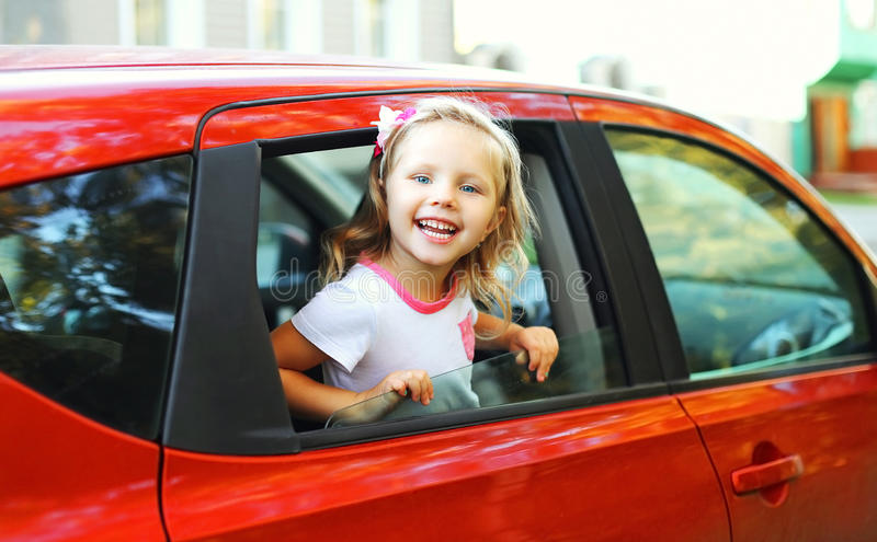 Portrait happy smiling little child sitting in red car. Portrait of happy smiling little child sitting in red car royalty free stock photography