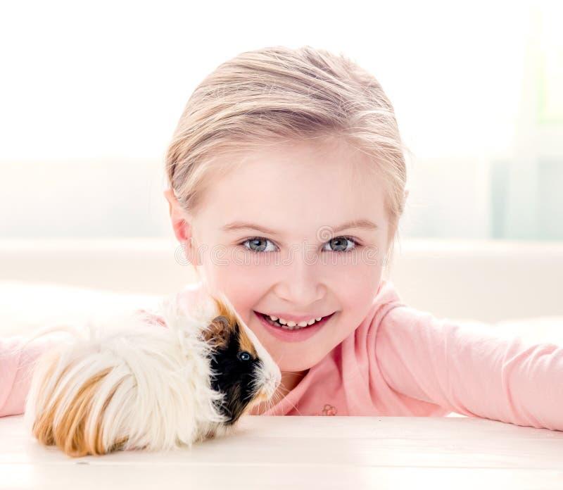 Smiling little girl hugging guinea pig stock photography