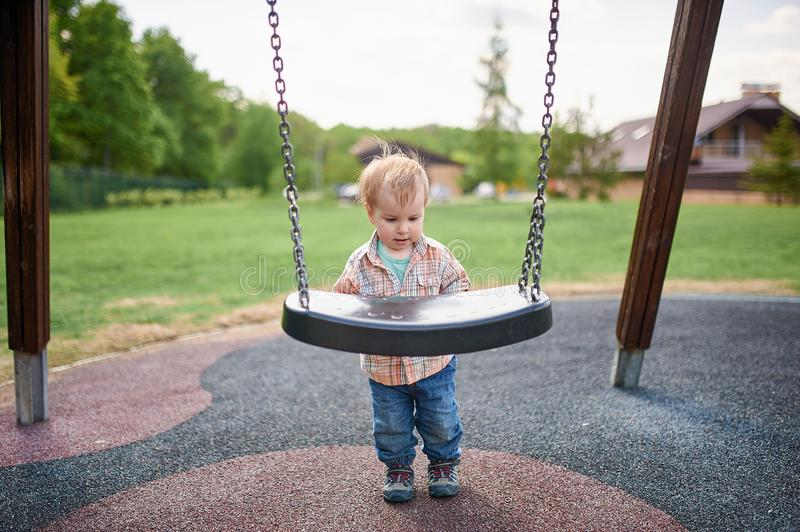 Portrait of happy smiling little toddler boy standing near the swings at playground outside on summer day. Portrait of happy smiling little toddler boy standing royalty free stock image