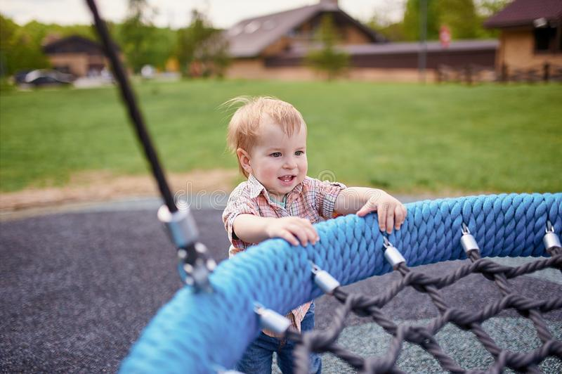 Portrait of happy smiling little toddler boy standing near the swings at playground outside on summer day. Portrait of happy smiling little toddler boy standing stock photos