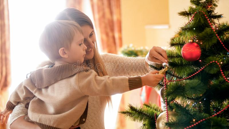 Portrait of happy smiling mother with her child decroating Christmas tree at morning royalty free stock photo