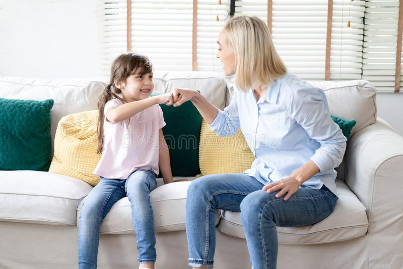 Portrait of happy smiling mother and daughter with pleasant smile greet happily and give fist bump to each other,have positive royalty free stock photo