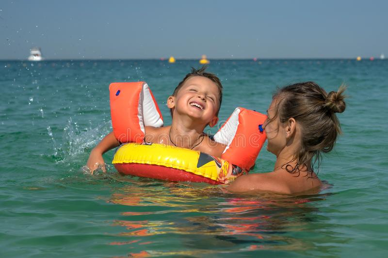 Portrait of happy smiling mother and son at sea, outdoor. Concept of friendly family. stock photo