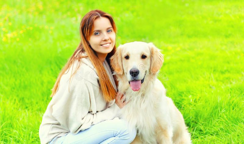 Portrait happy smiling owner with Golden Retriever dog together on grass in sunny summer royalty free stock photo