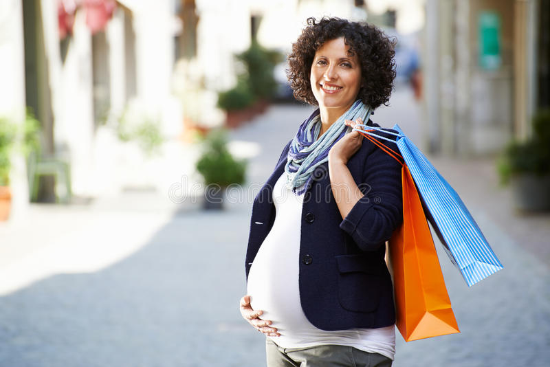 Portrait of happy and smiling pregnant woman shopping stock photos