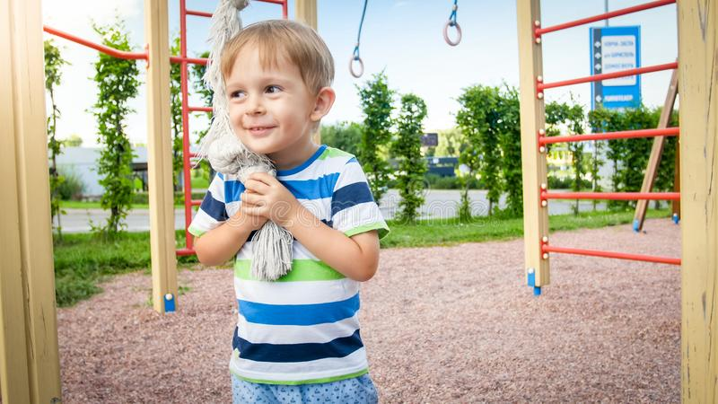 Portrait of happy smiling toddler boy playing with big rope for climbing on the children palyground at park. Active and royalty free stock image