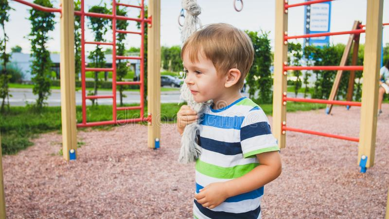Portrait of happy smiling toddler boy playing with big rope for climbing on the children palyground at park. Active and. Portrait of happy smiling toddler boy stock photos