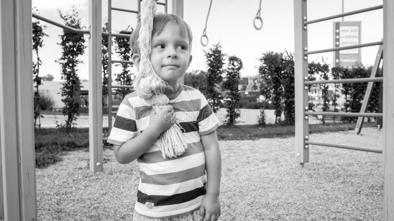 Portrait of happy smiling toddler boy playing with big rope for climbing on the children palyground at park. Active and. Portrait of happy smiling toddler boy royalty free stock photos