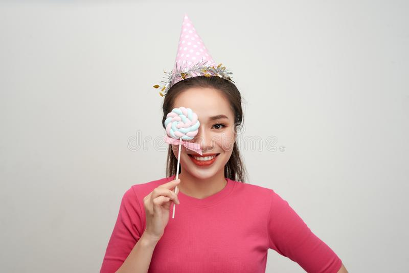 Portrait happy smiling woman in a birthday cap closes her eye with a lollipop on stick over pink background.  stock photography