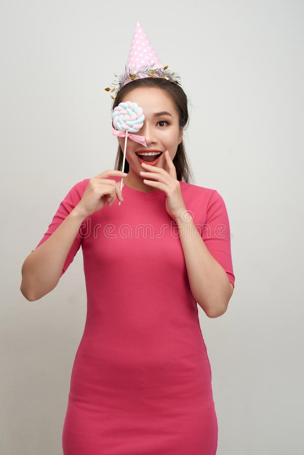 Portrait happy smiling woman in a birthday cap closes her eye with a lollipop on stick over pink background.  royalty free stock photo