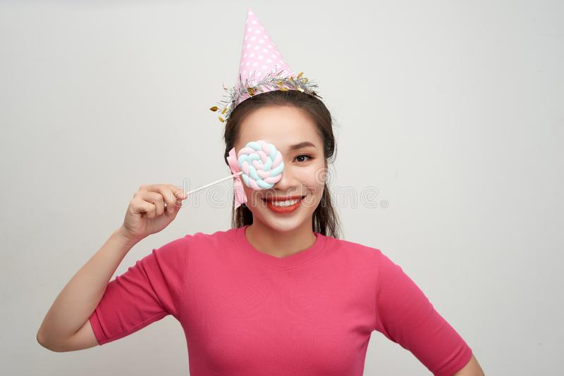 Portrait happy smiling woman in a birthday cap closes her eye with a lollipop on stick over pink background.  royalty free stock image