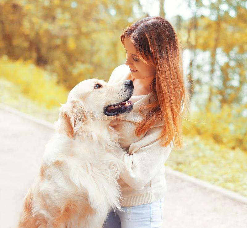 Portrait happy smiling woman with Golden Retriever dog looking at each other. In park royalty free stock photography