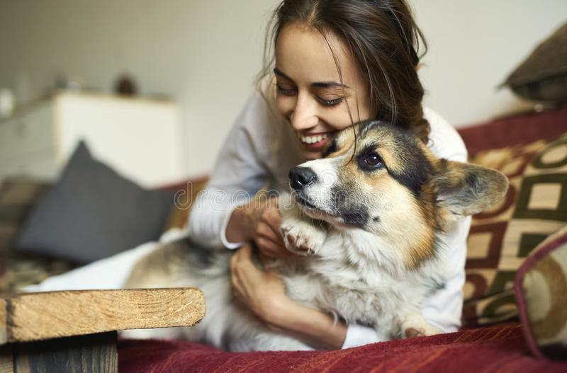 Portrait of happy smiling woman with her cute Welsh Corgi dog lying on couch at home. stock photography