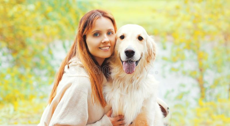 Portrait happy smiling woman with her Golden Retriever dog together in sunny autumn stock photography