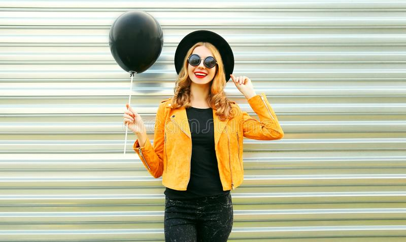 Happy smiling woman holding black helium air balloon. Portrait happy smiling woman holding black helium air balloon in round hat, yellow jacket on metal wall royalty free stock images