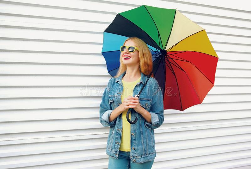 Portrait happy smiling woman holding colorful umbrella on white wall royalty free stock photos