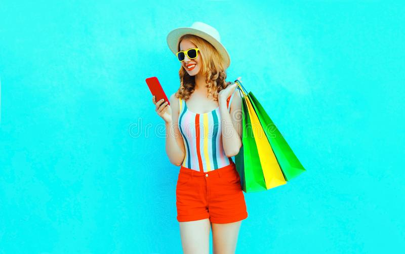 Portrait happy smiling woman holding phone with shopping bags in colorful t-shirt, summer straw hat, sunglasses, red shorts. On blue background stock photos