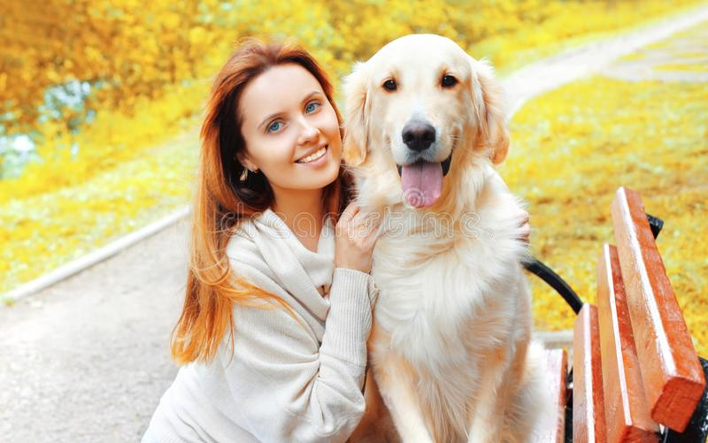 Portrait happy smiling woman hugging her Golden Retriever dog in park royalty free stock photos
