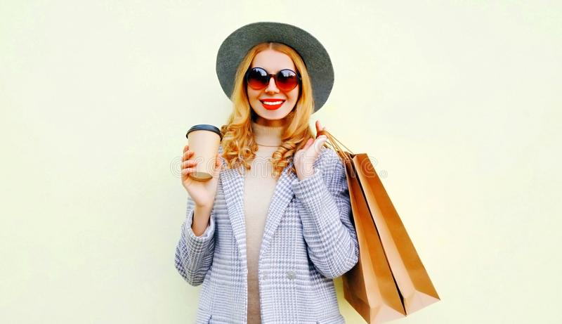 Portrait happy smiling woman with shopping bags, holding coffee cup, wearing pink coat, round hat on background stock photo