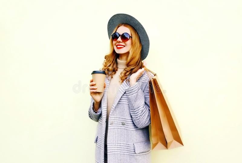 Portrait happy smiling woman with shopping bags, holding coffee cup, wearing pink coat, round hat royalty free stock photography