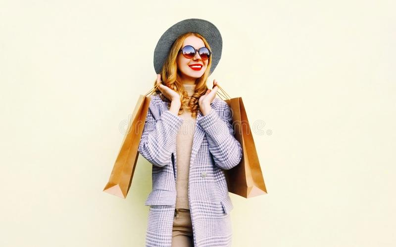 Portrait happy smiling woman with shopping bags in pink coat, round hat on  background royalty free stock images