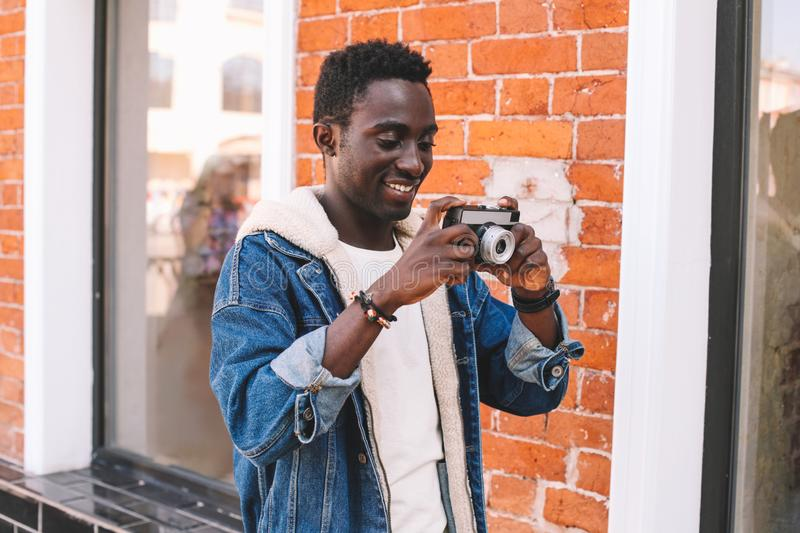 Portrait happy smiling young african man with vintage film camera taking picture walking on city street over brick wall. Background royalty free stock photography