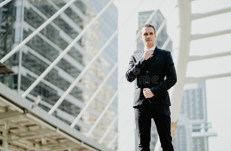 Portrait of happy smiling young businessman in a stylish suit standing and adjusting his neck tie on front building office stock images