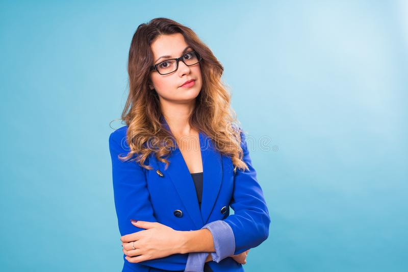 Portrait of happy smiling young cheerful businesswoman in glasses over blue background. Caucasian brunette model in royalty free stock photography