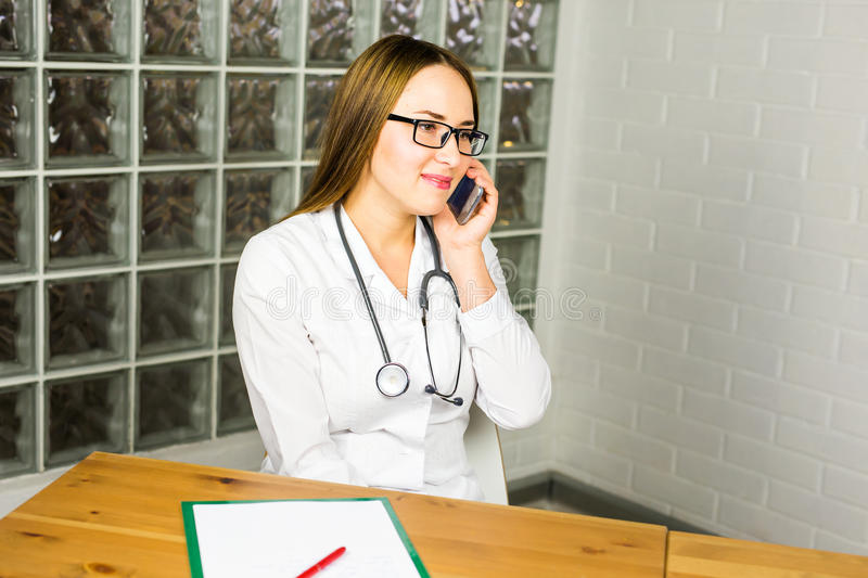 Portrait of happy smiling young doctor with cellphone.  royalty free stock photography