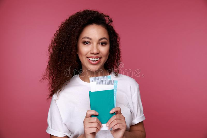Portrait of a happy smiling young girl holding passport and travelling tickets isolated over background stock image