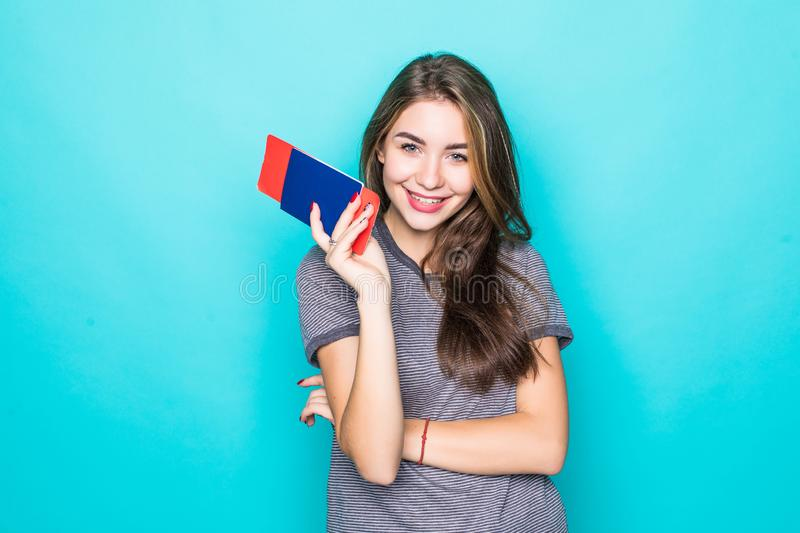 Portrait of a happy smiling young girl holding passport and travelling tickets isolated over blue background. Portrait of happy smiling young girl holding stock photo