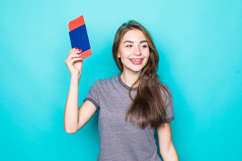 Portrait of a happy smiling young girl holding passport and travelling tickets over blue background. Portrait of happy smiling young girl holding passport and stock image