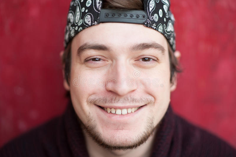 Portrait of happy smiling young man in a baseball cap and sweater on a red background royalty free stock photography