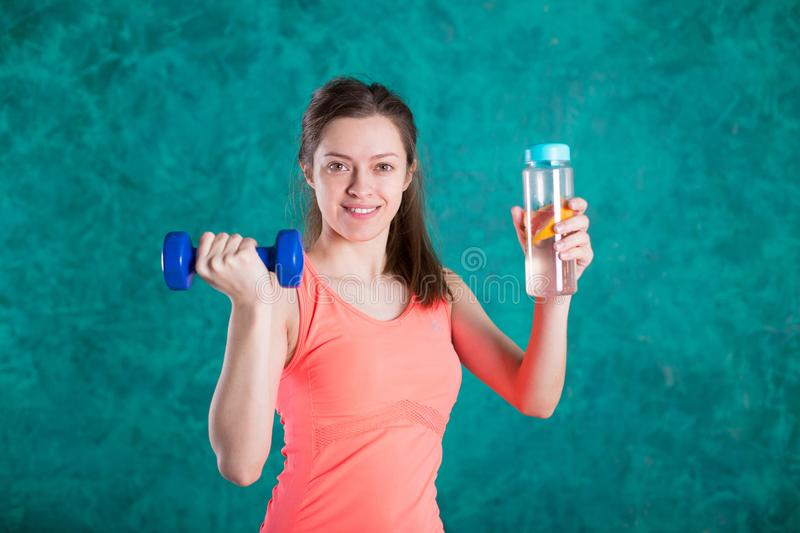 Portrait of happy smiling young woman in fitness wear with bottle of water and dumbbells, over turquoise background royalty free stock photo
