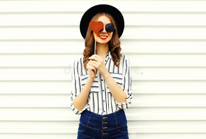 Portrait happy smiling young woman hiding her eye with red heart shaped lollipop in black round hat, white striped shirt on white. Wall background stock images