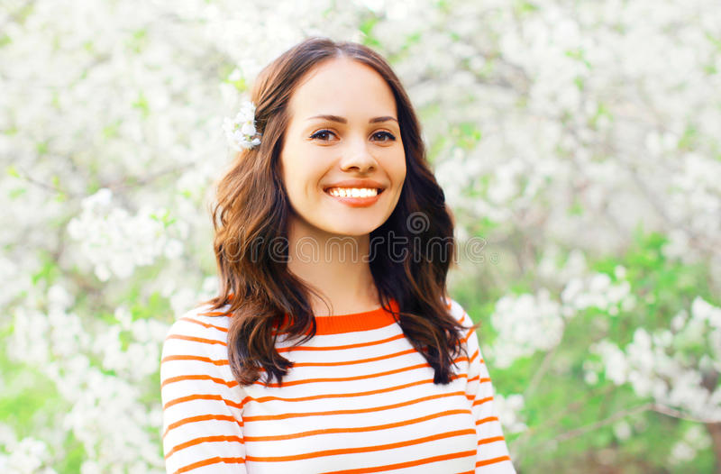 Portrait happy smiling young woman over white spring flowers stock photos
