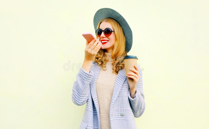 Portrait happy smiling young woman with smartphone using voice command recorder or calling, wearing coat jacket, round hat on wall stock image