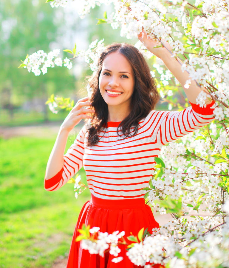 Portrait happy smiling young woman with spring flowers in garden stock photos