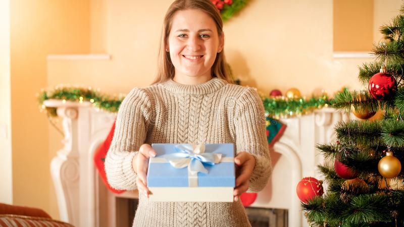 Portrait of happy smiling young woman in wool sweater holding Christmas gift in box and showing it in camera. Perfect royalty free stock photo