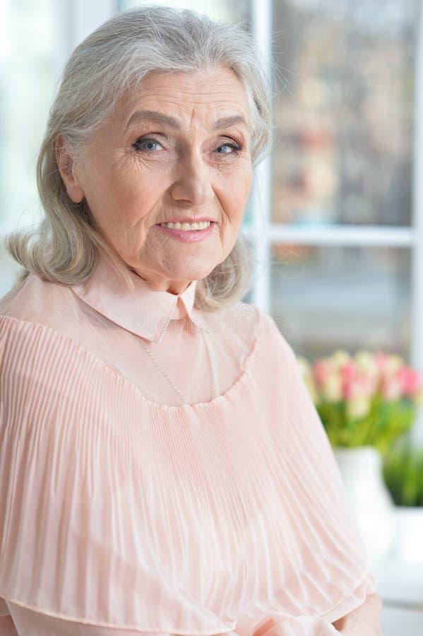 Happy smilling senior woman posing at home stock photos