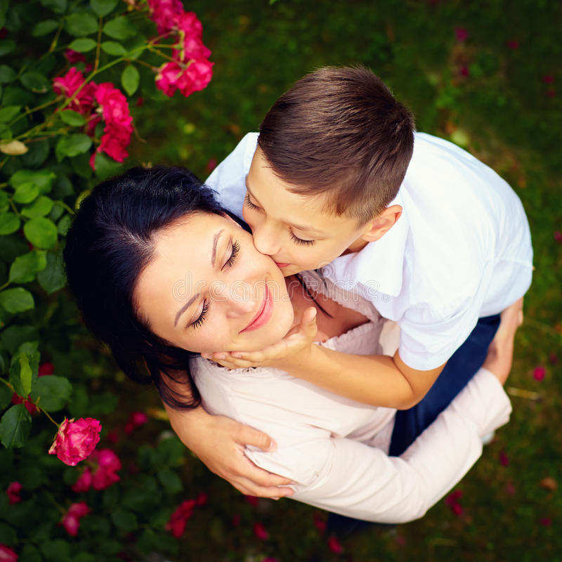 Portrait of happy son kisses mother in spring garden, top view stock photos