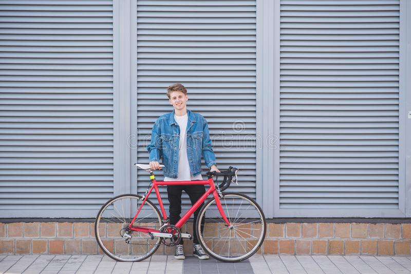 Portrait of a happy, stylish young man in a jeans jacket and a red bicycle on the background of a gray wall royalty free stock images